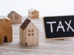 Property tax concept with model of houses with tax sign on wooden table