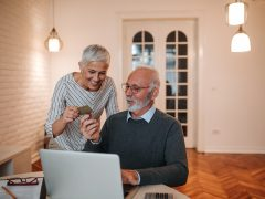 A beautiful happy senior couple using their credit card to order some goods on the internet.