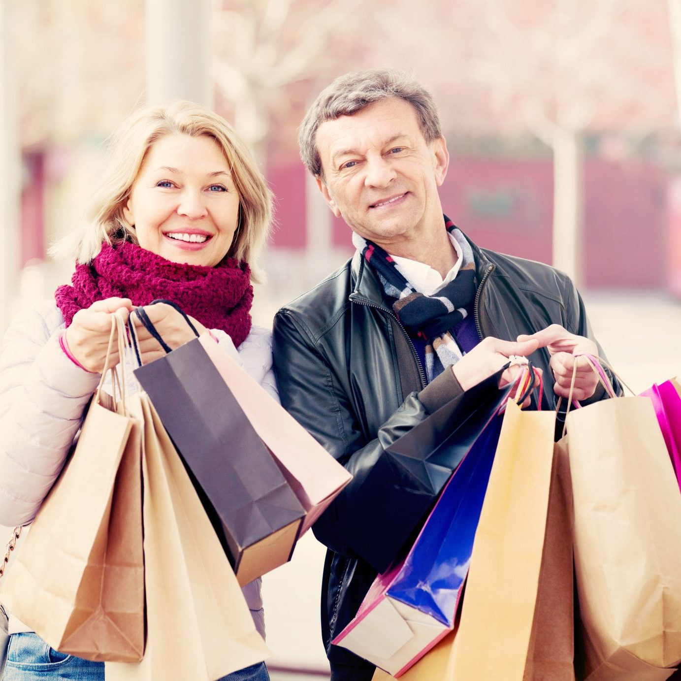 Happy smiling elderly spouses with shopping bags in spring day